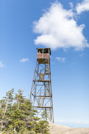 a woman enjoys the view from an old fire tower located on Hurricane Mountain in the Adirondacks of New York