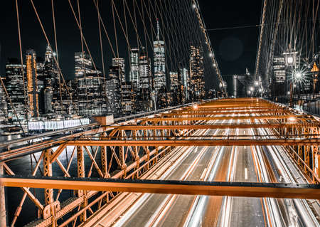 Long exposure of traffic along the Brooklyn Bridge night rush hour with lower Manhattan in view