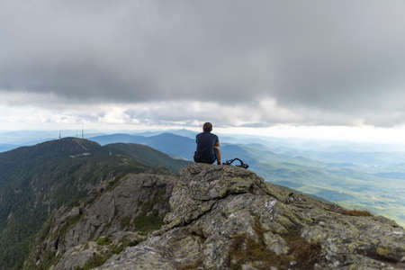 Man contemplates while atop a ridge line in Mount Mansfield in Vermont during the summer