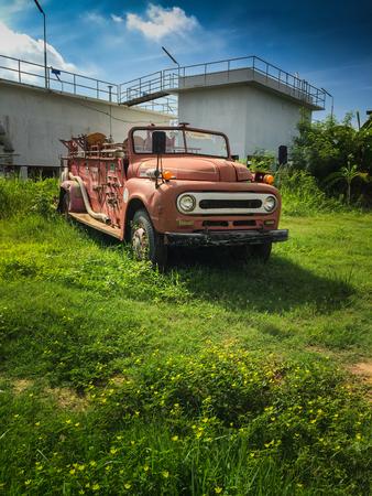 antique fire truck: old fire truck dead in garden Stock Photo