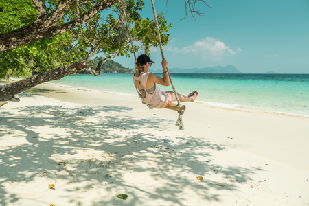 women play a swing at beach Stock Photo