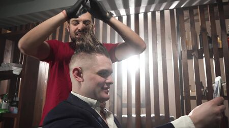 Vloger in barbershop. hairdresser or barber in red T-shirt and black gloves poses customer mohawk. After that, the client says something to camera.