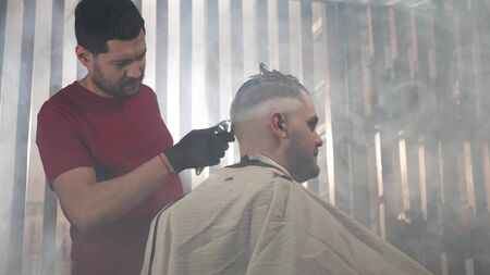 Side view of barber in black gloves and red t-shirt. The hairdresser shaves the nape of the client. A lot of smoke around.