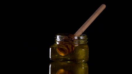 Honey dripping from honey dipper on black background. Healthy organic Thick honey dipping from the wooden honey spoon..