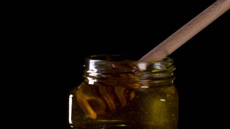 Close up tasty honey dripping from honey dipper in a jar. Tasty footage