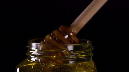 Close up tasty honey dripping from honey dipper in a jar.