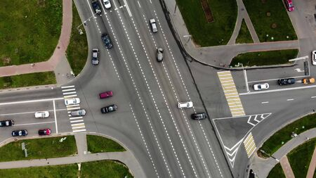 aerial view of road junction or road intersection in city with cars turning left and righ