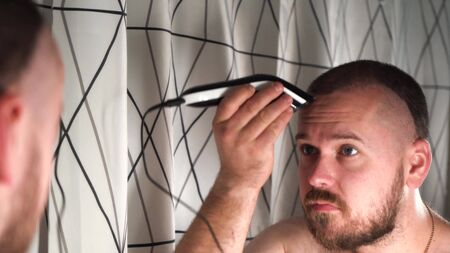 handsome man in the bathroom shaves his head himself with an electric razor. Stockfoto