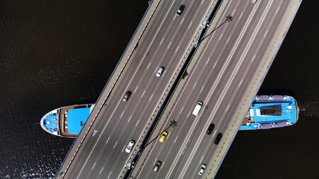 top view of bridge with moving cars, under which large blue-white cruise liner