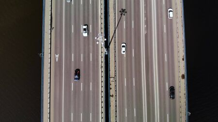 Top down aerial view on 11 lanes bridge with lot of cars and buses. Fly low