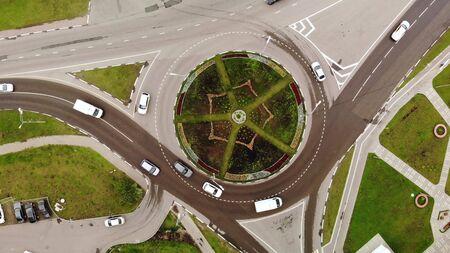 Cars after rain drive on the roundabout road aerial top down view