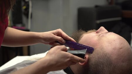 Womens hands trim the beard of bearded man with purple comb and black electric razor.