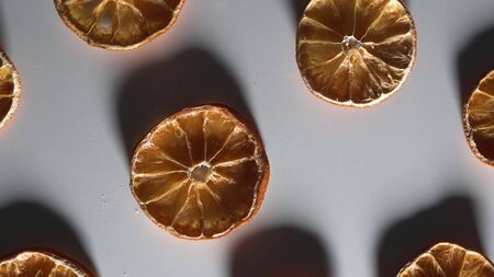 Low key light with long shadows. Dry slices orange on white table top down view rotate. Stockfoto