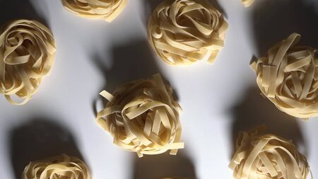 Low key footage lighting. pasta nests spin on a white table. Top view down on pasta.