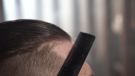 Following shot of comb on hair. Barbershop in city.