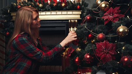 Young beautiful girl or woman in a red plaid shirt decorates a Christmas tree for Christmas or New Year