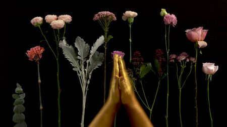 Gold hands clap on black background with flowers lay on the table. Nice footage of woman hands gesture Stockfoto