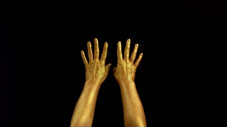 Nice footage of woman gold hands gesture. Black background. Hands in gold color paint on black background