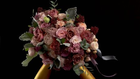 Woman gold hands take bouquet and lift it to camera. Close up of bouquet. Hands painted in gold color