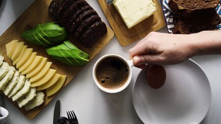 Perfect morning with coffee on the table. Top view down for breakfast with cheese, avocado, butter, brown bread, egg. Girl's hand puts a cup of black aromatic coffee on the table