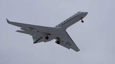 Moscow, Russia - 07 01 2020: White airplane Gulfstream G550 landing in Moscow city airport. Cloudy day.