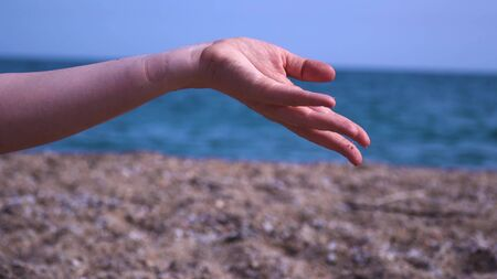 Taking sand in both hands and sand running through fingers