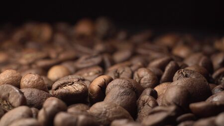 Super extreme close up footage of coffee beans with black background on the table with black background. Camera slowly goes forward on dolly slider.