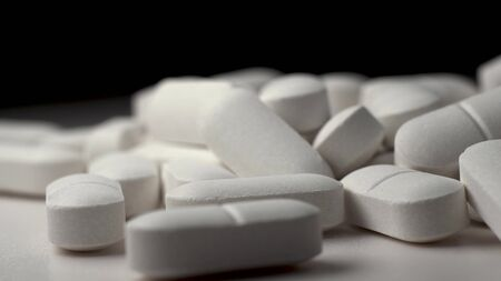Many white pills rotate. Beautiful macro footage. The invention of tablets from coronovirus. Black background Stockfoto