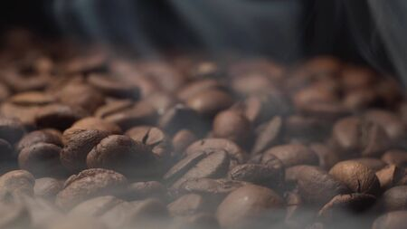 Gorgeous shots of close up coffee roast and smoke coming from coffee beans on black background Stockfoto - 144040043