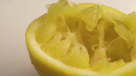 Squeezed lemon lies on a white table. The white table is spinning, or the camera is spinning around the table