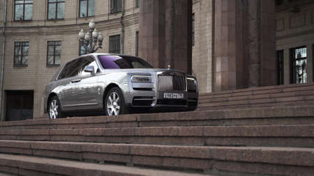 Moscow, Russia - 13 03 2020: The majestic Rolls Royce Cullinan in his path. expensive car drove up to the palace with huge columns and stands waiting for the businessman.