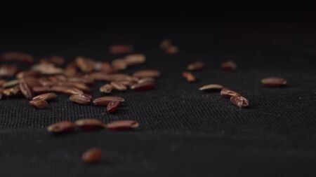 Brown rice falls beautifully on spinning black table. Brown rice is used in cooking as side dish in expensive restaurants and cafes. Rotating around falling dark rice with black background.