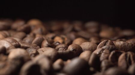 Super extreme close up footage of coffee beans with black background on the table. Camera slowly goes back on dolly slider Stockfoto