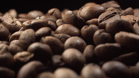 Nice falling coffee beans on rotating coffee beans. Cinematic footage of roasted coffee extreme macro shot close up Stockfoto