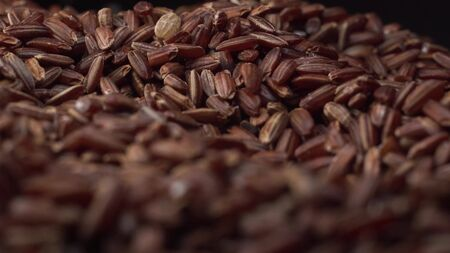 Brown rice lies on table and camera rotate around it. Rice is the main food for all people, macro footage.