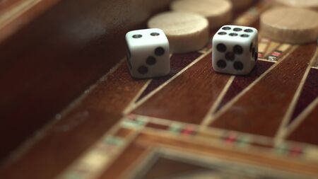 Close-up of a game of backgammon. Macro footage of how dice are thrown. On dice, the number eight is dropped. Stockfoto