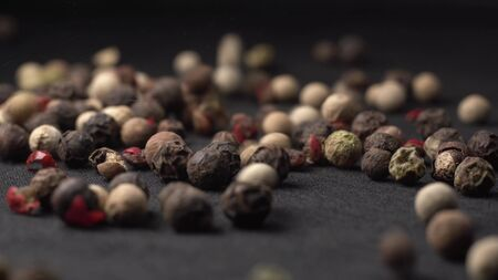 Mixed peppercorns falling on black table in kitchen with black background