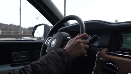 Moscow, Russia - 13 03 2020: A man drives Rolls Royce Culinan. View of hands on steering wheel. Redactioneel