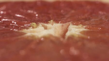 Close up macro shot of rotating grapefruit on the table. Extreme close up footage of spinning fruit Stockfoto