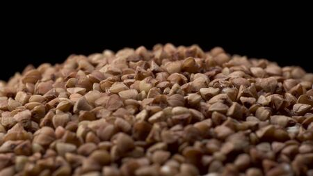 Rotating macro footage of buckwheat with falling down on black table with black background. Buckwheat is tasty and good food like a dish.