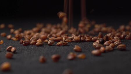 Buckwheat tea pours onto a rotating black table with a black background. golden buckwheat tea for health.