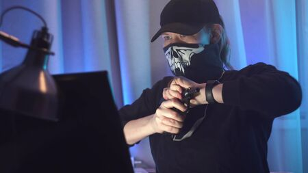 Female hacker sitting at her desk, working. Police siren in window. Woman see it, put on mask, take gun and escape from crime scene. Stockfoto