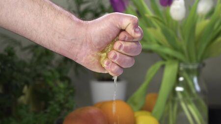 Male hand squeeze lemon with one hand. On background there are fruits and plants. Stockfoto