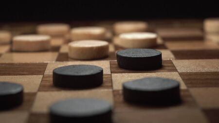 Game of checkers. Close up footage of player make his turn with black chip on black background.