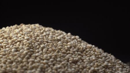 White beautiful quinoa strew on a black background. Quinoa is healthy and sport product for dishes