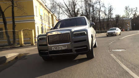 Moscow, Russia - 13 03 2020: Rolls Royce Cullinan is moving down the street. The driver is carrying a businessman. Expensive status car drives through intersection and turns left. Stockfoto - 144182522