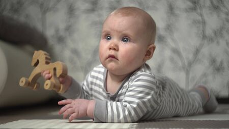 Little beautiful blond baby in striped pajamas plays on floor with wooden horse and tries to eat it Stockfoto