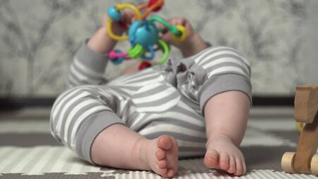 Baby feet in the frame. The kid in striped pajamas is played with a childrens colored toy on the floor. Stockfoto