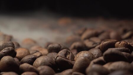 Nice and cinematic footage of roasted coffee beans. Camera slowly fly above coffee beans with smoke with black background. Stockfoto
