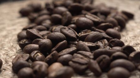 Beautiful brown roasted coffee beans lie on canvas table, camera flies over raw drink.